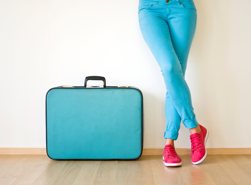 Young woman stands beside old fashioned suitcase, ready to travel f