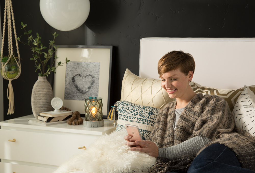 Woman texting in bed with Scentsy warmer on the table