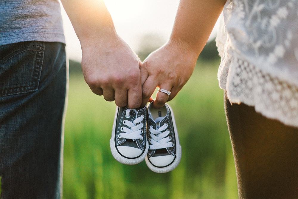 Photo of a couple holding baby shoes
