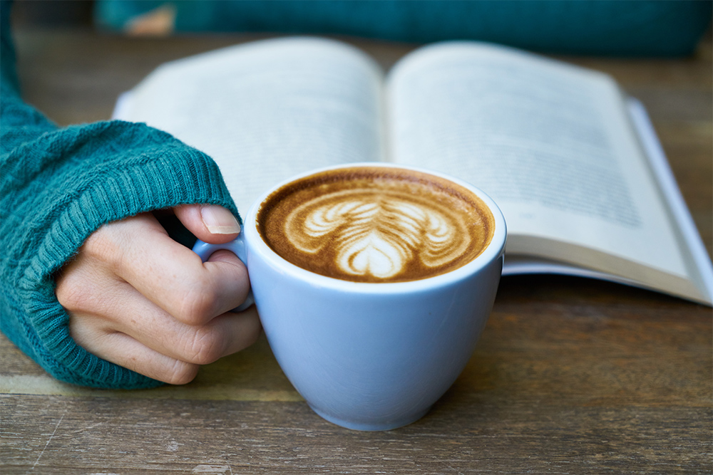 woman reading open book with coffee