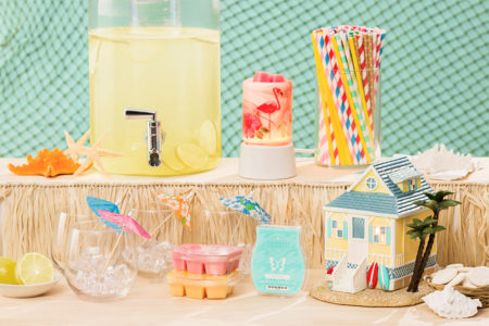 Photo of the scentsy's summer collection products in a beach party scene