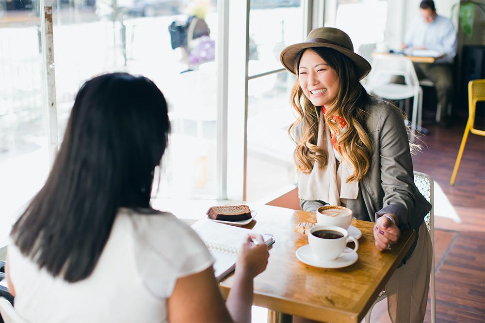 Scentsy counsultant happily talking to her friend over coffee