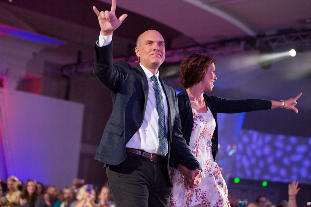 Heidi and Orville showing I love you signs to the Scentsy Family Renunion crowd