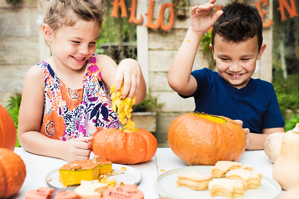 Photo of boy and girl carving pumpkins
