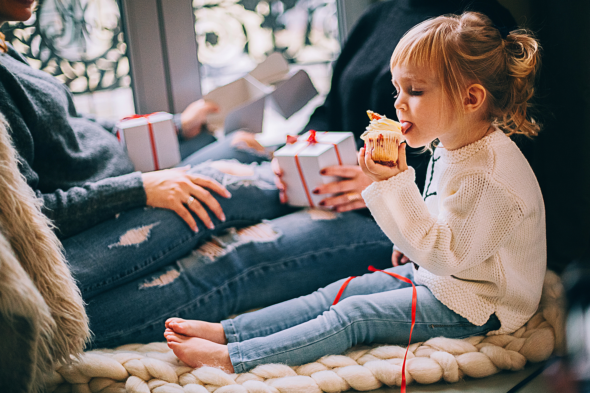 Photo of little girl eating holiday cupcakes with parents in the background