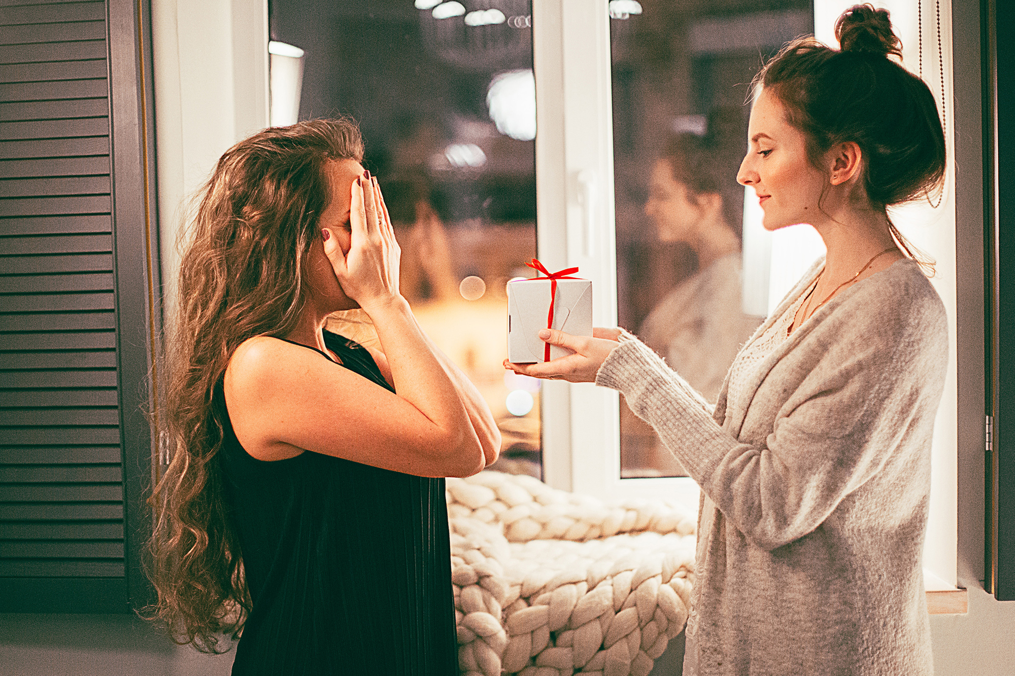 Photo of a woman giving her friend a christmas gift