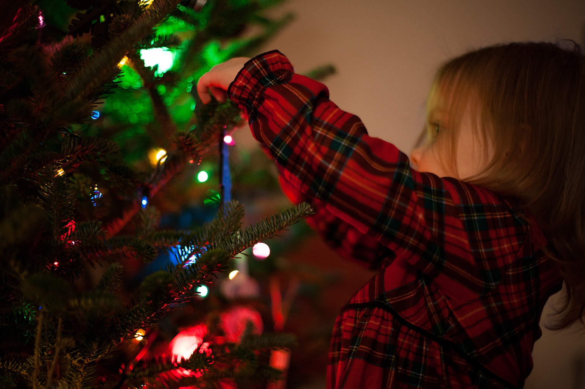 Photo of little girl hanging christmas ornament on the tree