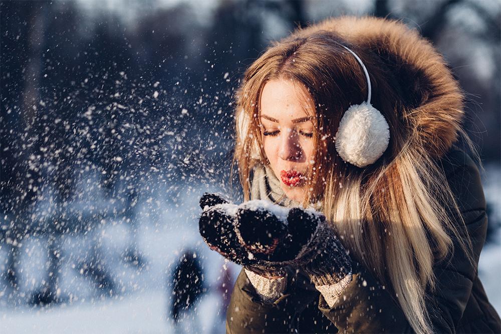 woman in seasonal dress blowing snow into air