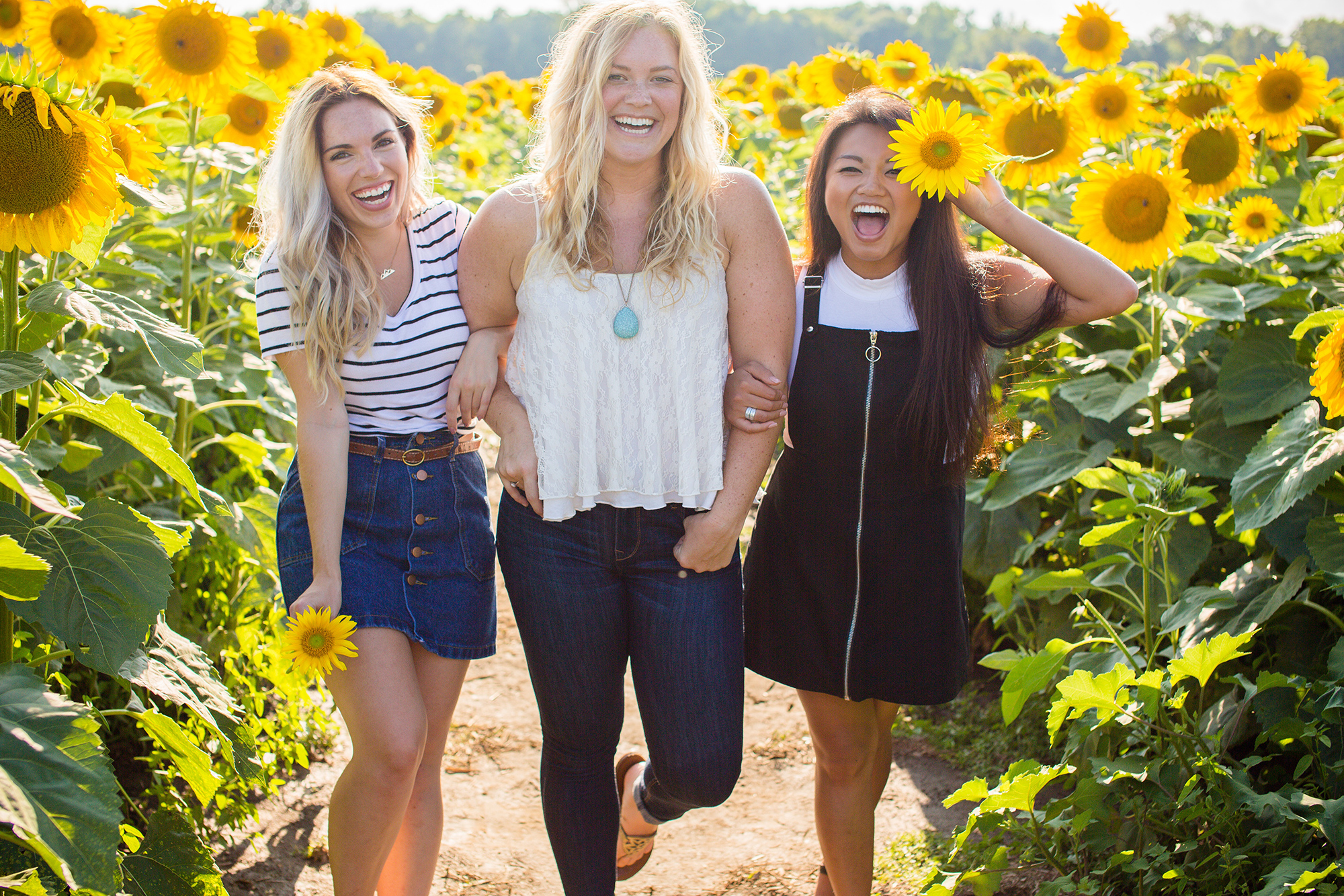 Friends laughing in field of flowers
