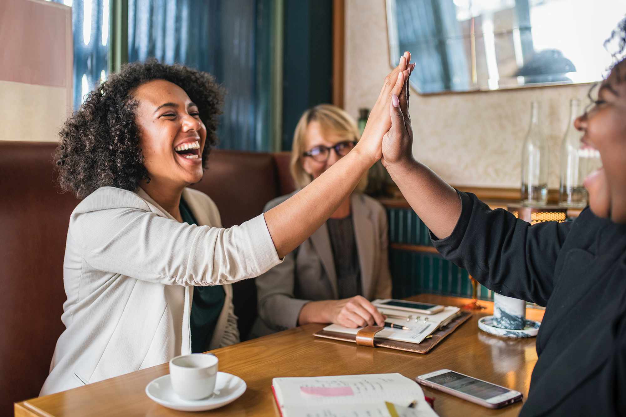 Two women high fiving each other